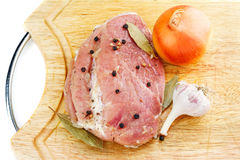 Raw meat before cooking with spices, onion and garlic on wood cutting board Royalty Free Stock Photo