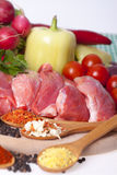 Raw meat, cut into pieces with pepper, cherry, radish, pepper a. Fresh pork with vegetables and spices on a wooden board. Raw meat, cut into pieces with pepper Royalty Free Stock Photo