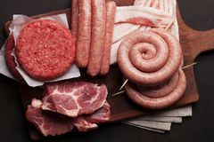 Raw meat and sausages. Raw meat, cutlet, bacon and sausages. Top view Royalty Free Stock Images