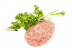 Raw meat cutlet with a sprig of parsley and rosemary on a white Stock Photos