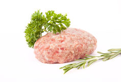 Raw meat cutlet with a sprig of parsley and rosemary on a white Stock Photography