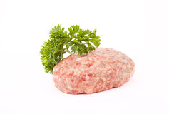 Raw meat cutlet with a sprig of parsley on a white background Stock Photos