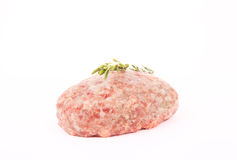 Raw meat cutlet with a sprig of  rosemary on a white background Stock Images