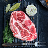 Raw meat on cutting board. Fresh raw meat on black wooden cutting board surrounded by spices, garlic and fork. Square crop Stock Images