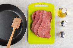 Raw meat on cutting board, frying pan, spatula, oil, condiments Stock Photo