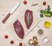 Raw meat on a cutting board with a knife for meat and herbs wooden rustic background top view close up. Raw meat on a cutting board with a knife for meat and Royalty Free Stock Photography