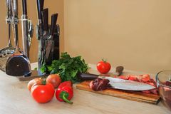 Raw meat on a cutting board with knife. Raw steak with herbs, oil knife for meat on a cutting board on wooden rustic background Royalty Free Stock Photo