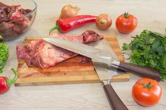 Raw meat on a cutting board with knife. Raw steak with herbs, oil knife for meat on a cutting board on wooden rustic background Royalty Free Stock Images