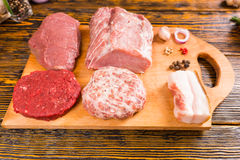 Raw meat on cutting board with pepper spice. Chunks and slices of raw beef and pork meat on cutting board with pepper spices and glass jar over table Stock Photography