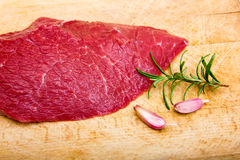 Raw meat on cutting board. Raw meat with rosemary and garlic on chopping board Royalty Free Stock Photography