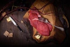 Raw meat on dark wooden background. Raw beef steak. Stock Photos