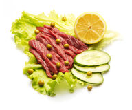 Raw meat decorated with lemon, cucumber, and salad Royalty Free Stock Photography