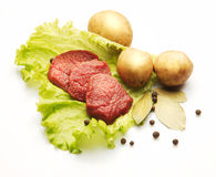 Raw meat decorated with potato, and salad. Over white background Royalty Free Stock Image