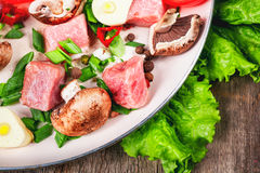 Raw meat in dish and frying pan, spices, knife on wooden table,. Vegetables, top view Stock Image
