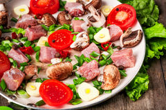 Raw meat in dish and frying pan, spices, knife on wooden table,. Vegetables, top view Royalty Free Stock Images