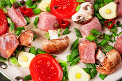 Raw meat in dish and frying pan, spices, knife on wooden table,. Vegetables, top view Royalty Free Stock Image