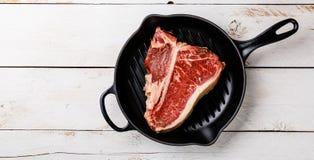 Raw meat Dry Aging Steak T-bone in cast iron frying pan