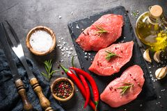 Beef steak with rosemary and spices on black background Stock Image