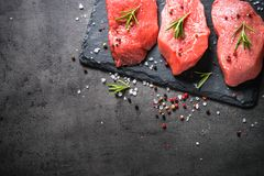 Beef steak with rosemary and spices on black background Stock Photography