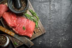 Raw meat. Fresh beef on a wooden tray with fragrant peppercorn and rosemary branches royalty free stock photography
