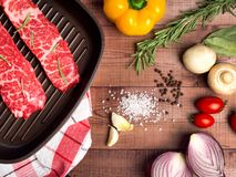 Raw meat in a frying pan on brown boards. Nearby spices, condime. Nts and vegetables. Top of view Royalty Free Stock Photo