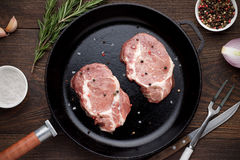 Raw meat on frying pan on wooden background with herbs and spices. stock photo