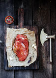 Raw meat with garlic and axe on wooden table. Style rustic. Selective focus Stock Photos