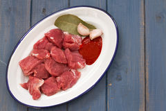 Raw meat with garlic on dish on blue background. Raw meat with garlic on dish on blue wooden background Stock Images