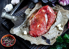 Raw meat with garlic and herbs and axe on wooden table. Style rustic. Selective focus Stock Image