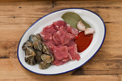 Raw meat with garlic and seafood on dish. On brown wooden background Royalty Free Stock Photo
