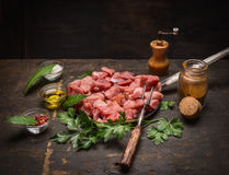Raw meat for Goulash preparation with oil and fresh herbs and spices on rustic wooden background. Raw meat Goulash preparation with oil and fresh herbs and royalty free stock photos