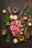 Raw meat for Goulash preparation with oil and fresh herbs and spices on rustic wooden background. Raw meat Goulash preparation with oil and fresh herbs and stock images