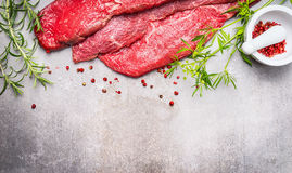 Raw meat for grill, BBQ or cooking with herbs and spices mortar on gray concrete background, top view. Border Royalty Free Stock Photo