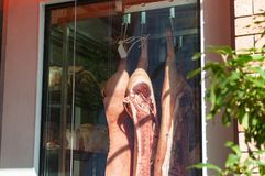 Raw meat hanging on display in butcher shop window Royalty Free Stock Photography