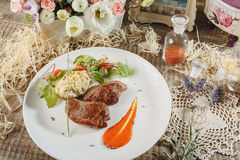 Raw meat with herbs, seasonings, tomato cherry, cucumbers and white souce cream on wooden round table. Row beef steak grill pan st. Close up horizontal image of Stock Photo