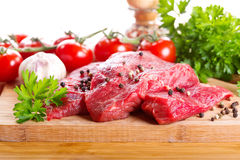 Raw meat with herbs and vegetables. On wooden board Stock Image