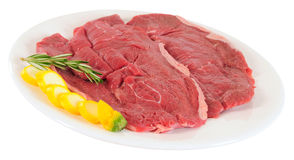 Raw meat. Isolated. Slices of raw meat with zucchini and rosemary Royalty Free Stock Photo