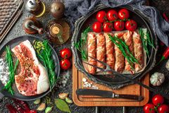 Raw meat on the kitchen. Table on a metallic background in a composition with cooking accessories Royalty Free Stock Image