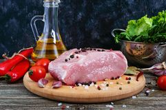Raw meat. A large piece of pork with spices and salt on a cutting board. On a wooden table Royalty Free Stock Image