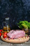 Raw meat. A large piece of pork with spices and salt on a cutting board. On a wooden table Royalty Free Stock Images