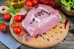 Raw meat. A large piece of pork with spices and salt on a cutting board. On a wooden table Royalty Free Stock Photo