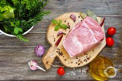 Raw meat. A large piece of pork with spices and salt on a cutting board on a wooden table. Top view Royalty Free Stock Images