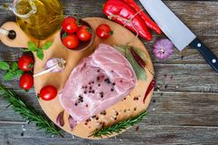 Raw meat. A large piece of pork with spices and salt on a cutting board. On a wooden table. Top view Royalty Free Stock Photos