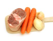 Raw meat of a leg and vegetables on kitchen bread Royalty Free Stock Photography