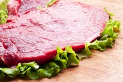 Raw meat on lettuce leaves. Wooden background Royalty Free Stock Photography