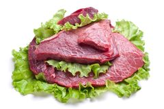 Raw meat on lettuce leaves. On white Royalty Free Stock Photo