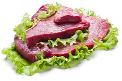 Raw meat on lettuce leaves. Isolated on white Stock Photo