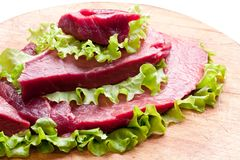 Raw meat on lettuce leaves. Wooden background Stock Photography