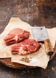 Raw meat and meat cleaver. Raw fresh meat and meat cleaver on dark background royalty free stock image