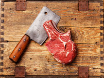 Raw meat and meat cleaver. Raw fresh meat and meat cleaver on wooden background stock photo